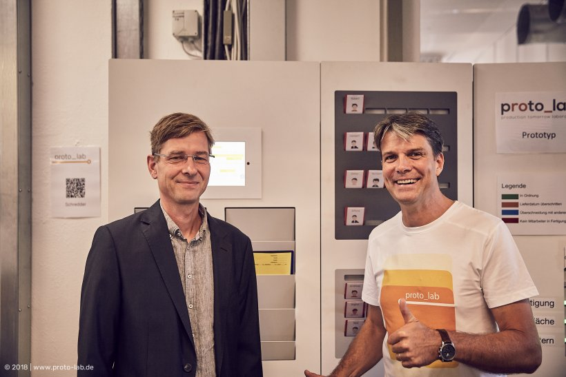 Georg Jahn und Prof. Dr. Oliver Kramer stehen vor der WEIGANG Tafel.