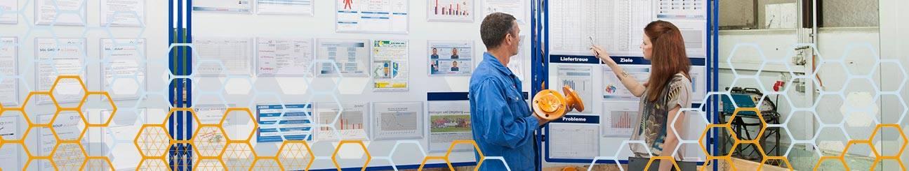 Menschen vor Visualisierungstafeln in Produktion für Shopfloor Management.